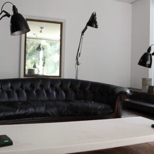 white room with 3 angle poise lamps, window and black sofa